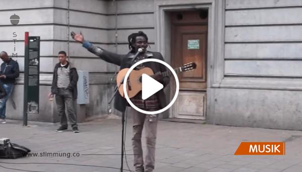 Der Straßenmusikant spielt gerade Reggae als eine unbekannte Frau ihm die Show stiehlt