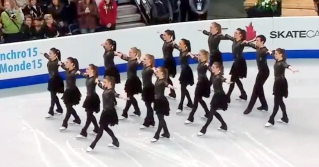 Sechszehn Eisläufer stehen in einer Linie – als die Musik beginnt machen sie etwas Außergewöhnliches
