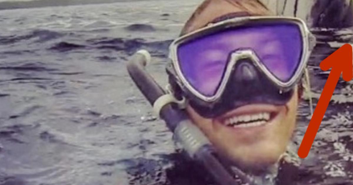 Der Taucher macht ein Selfie über Wasser. Als er auf dem Foto sieht, was hinter ihm ist, macht der große Augen.