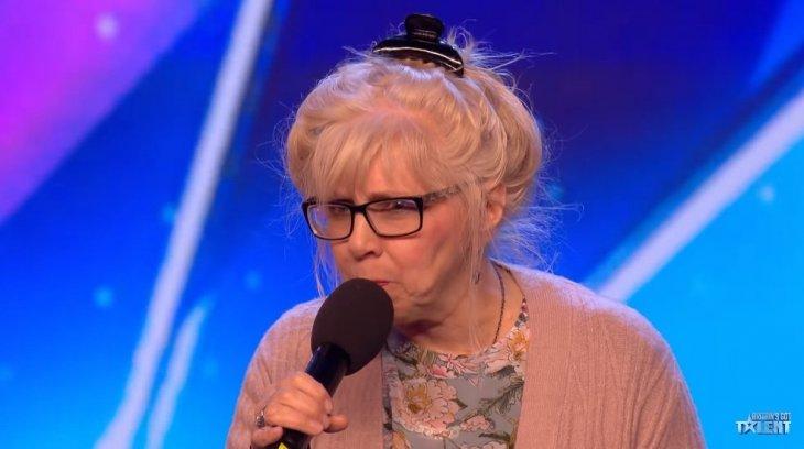 Eine ältere Dame betritt die Bühne und zeigt, dass sie ein Rockstar ist