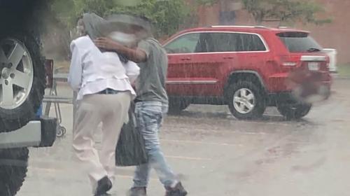 Jugendlicher schützt ältere Dame vor Regen, unbewusst, dass die Polizei ihn und seine Familie dafür anhalten wird