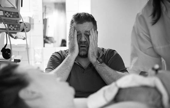 Geburtsfotografin teilt emotionale Reaktion von Papa.