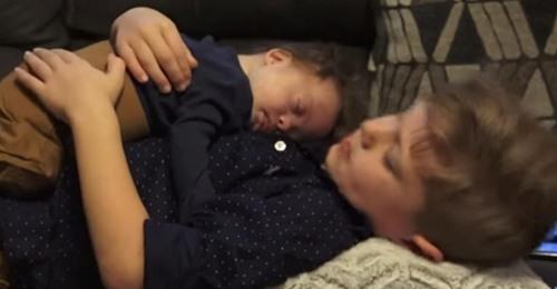 Liebevoller Bruder singt ein Lied für seinen kleinen Bruder mit Down-Syndrom