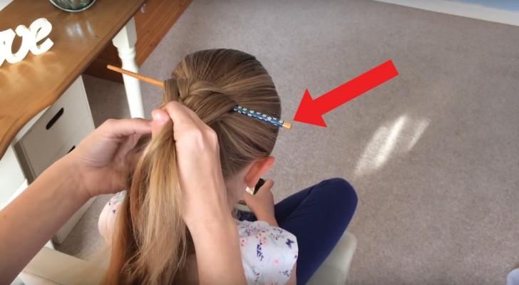 Sie steckt einen Stab durch die Haare und beginnt einen Zopf zu flechten: als sie ihn wieder rauszieht, sieht die Frisur wundervoll aus